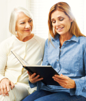 caregiver and senior woman reading book